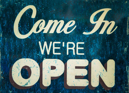 come in we are open sign hanging on a window door outside a restaurant, store, office or other Stock Photo
