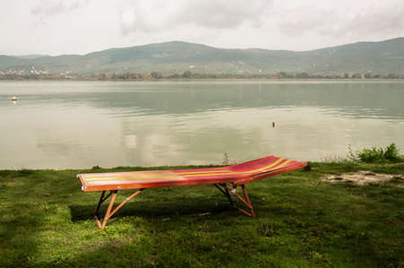 Isoleted Sunbed on the small beach near a lake in Umbria, Italy