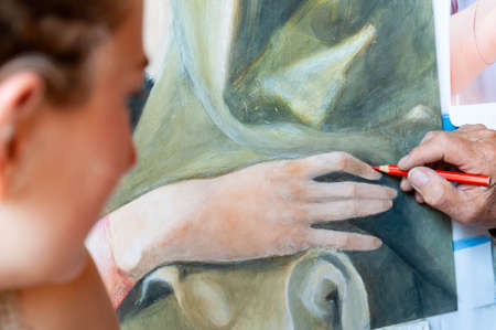 A painter teachs to paint to a young woman in his workshop, Italy
