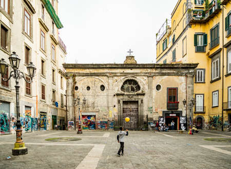 NAPLES, ITALY - MAY 16, 2015 - A boy played with a ball on Banchi Nuovi square, with its traditional architecture in the historic center of Naples, Italy