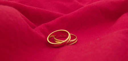 two wedding rings on a red cloth background