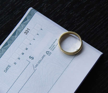 a ring and an open checkbook on a black desk Stock Photo