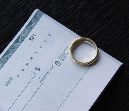 checkbook: un anillo y una chequera abierta sobre un escritorio negro  Foto de archivo