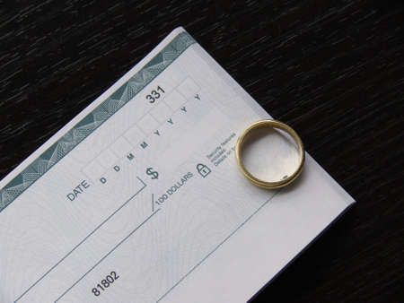 financial planning married: a ring and an open checkbook on a black desk Stock Photo
