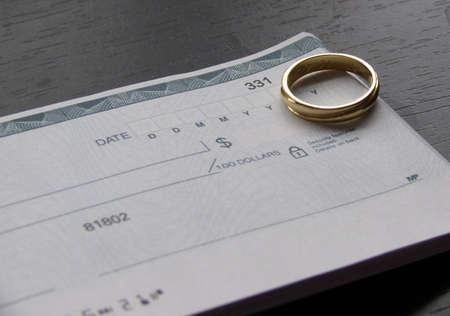 chequera: un anillo y una chequera abierta sobre un escritorio negro  Foto de archivo