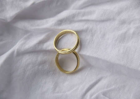 two wedding rings on a white cloth background Stock Photo