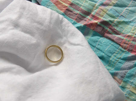 evocative: objects evocative of a joung bride: a wedding ring over a background of white and colourful cloth
