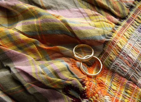 two wedding rings on a colourful cloth background Stock Photo