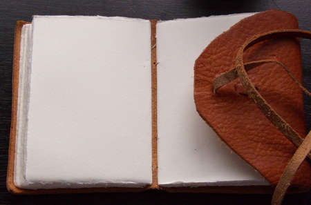a journal with leather cover on a black desk