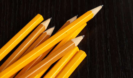 pencils, sharpened and unsharpened, on a black desk