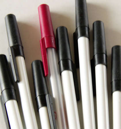one red pen among many black ones Stock Photo