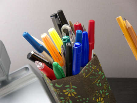 close-up on a corner of a desk, part of a lamp is visible and various pens, markers and pencils Stock Photo