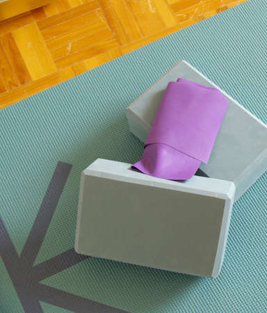 newage: yogapilates props: a mat, two blocks and an elastic band on a wooden floor Stock Photo
