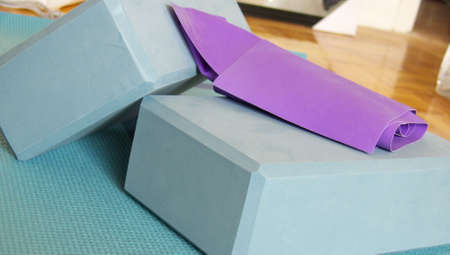 yogapilates props: a mat, two blocks and an elastic band in a home