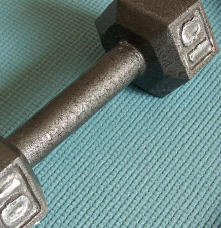 a 10 lbs iron dumbbell on a blue fitness mat