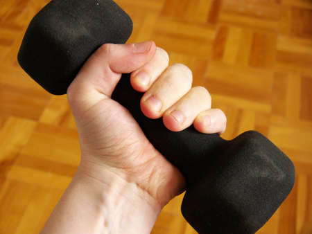 a womans hand holding a dumbbell in a home environment