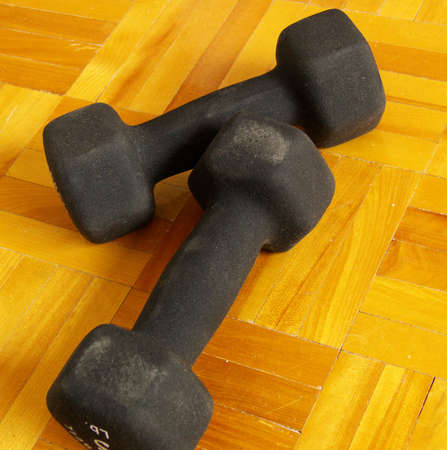 two dumbbels on a hard wood floor