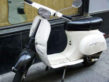 an old white vespa parked on theside of an italian alley Stock Photo