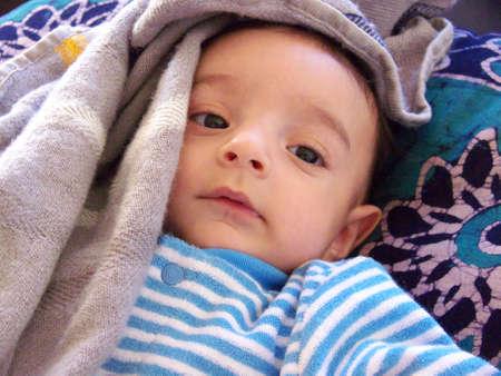 niño abrigado: tres meses de edad bebé con un manto de luz alrededor de su cabeza  Foto de archivo