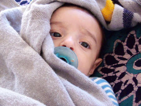 three month old baby with a light blanket around his head and a soother