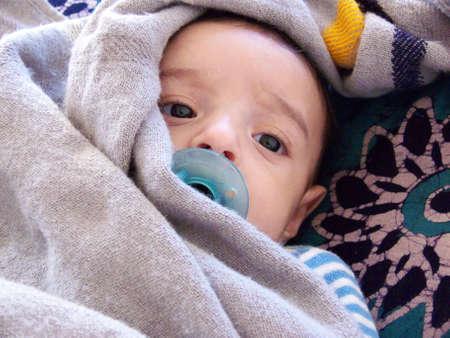 niño abrigado: tres meses de edad bebé con un manto de luz alrededor de su cabeza y un chupete  Foto de archivo