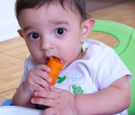 six month old baby eating a carrot