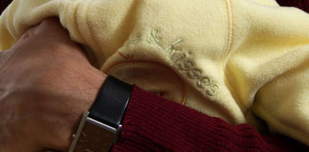close-up on hand of father of indian ethnicity holding his  in yellow pajamas