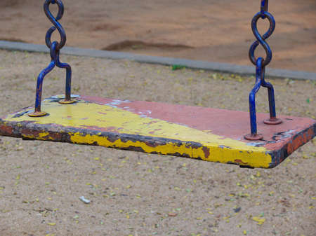 old and ruined wooden swing in a playground