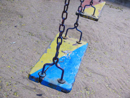 two old-fashioned wooden swings in a playground