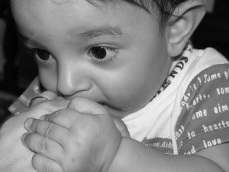 seven month old boy holding his mothers hand near his mouth