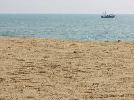ocean beach with boat near the horizon