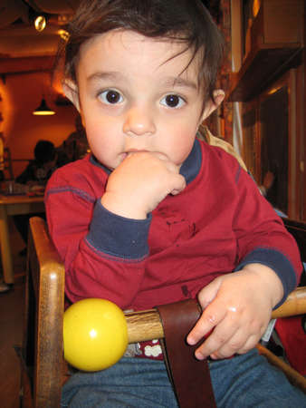 portrait of  boy sitting on a wooden high chair in a restaurant