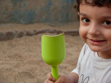 little boy holding a toy shovel at the playground  Stock Photo
