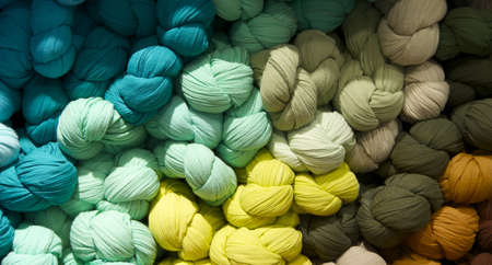 Braided scarves arranged by color in tones of blue, green and yellow