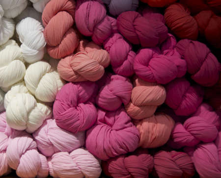 Braided scarves arranged by color in tones of white, pink and red