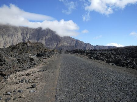 Road through black lava field Standard-Bild