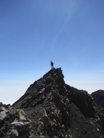 Man standing on top of volcano Standard-Bild