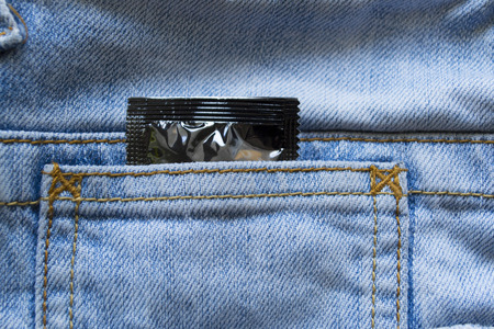 Blue denim jeans pocket with condom photo