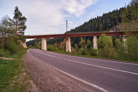 railway bridge across the road in the mountains is a beautiful 스톡 콘텐츠