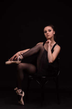 pointes: Silhouette ballet dancer in black swimsuit at the studio background