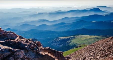 Hazy clouds linger in the many layers of Colorado Mountains, as viewed from an elevation of 13500 feet on Mt Evans Colorado