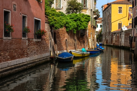 Peaceful reflections on a Venice Canal with boats waiting