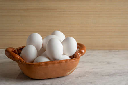 White egg in a bowl or clay pot, on a marble bar and wooden background. With space for advertising at the top.