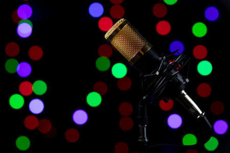 Base-mounted, corded professional tabletop microphone with dynamic lighting and colored lights in the background.