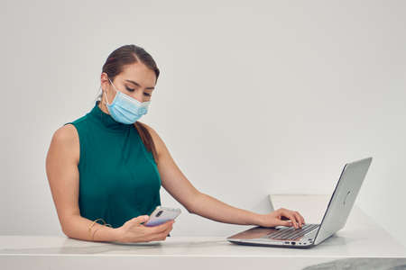 Executive woman checking emails on computer, wearing mask due to the new normal due to the covid-19 pandemic