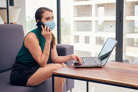 Woman with mouth cover working at home due to the new normal due to the covid-19 pandemic