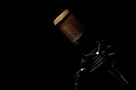 Professional tabletop microphone with cable and mounted on its base with a black background. Banque d'images