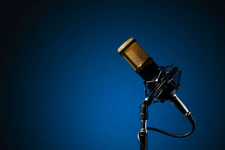 Stand-mounted corded tabletop microphone with a blue gradient background.