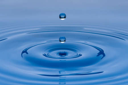 Drops of blue water frozen in the air and forming waves on the liquid surface, with rocks or stones in the background.