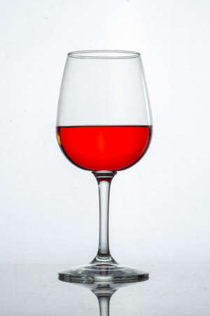 Glass cup with red liquid and white background Banque d'images
